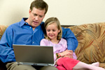 Father and Daughter Searching Online for Lawn Conversion Rebates